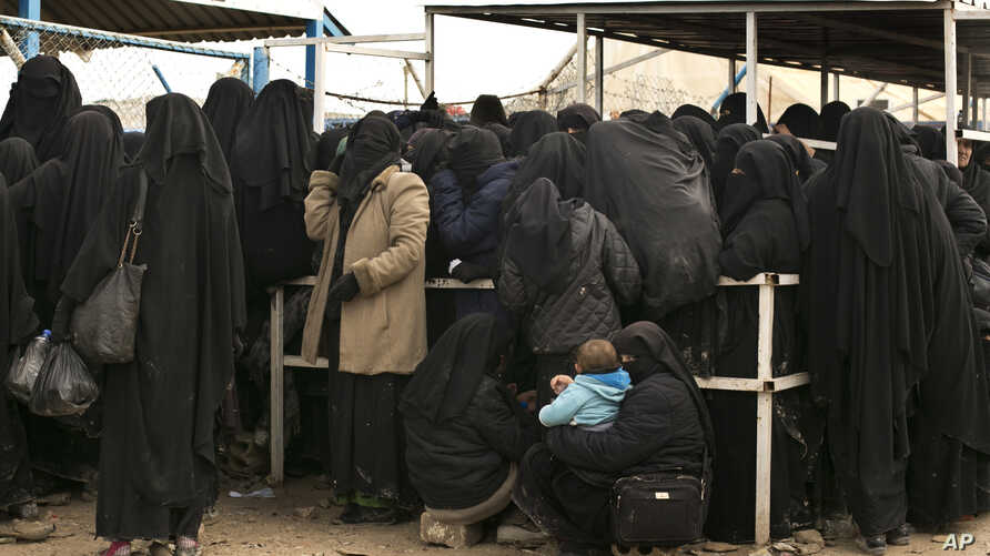 In this Sunday, March 31, 2019, photo, women line up for aid supplies at Al-Hol camp in Hassakeh province, Syria. The camp is…