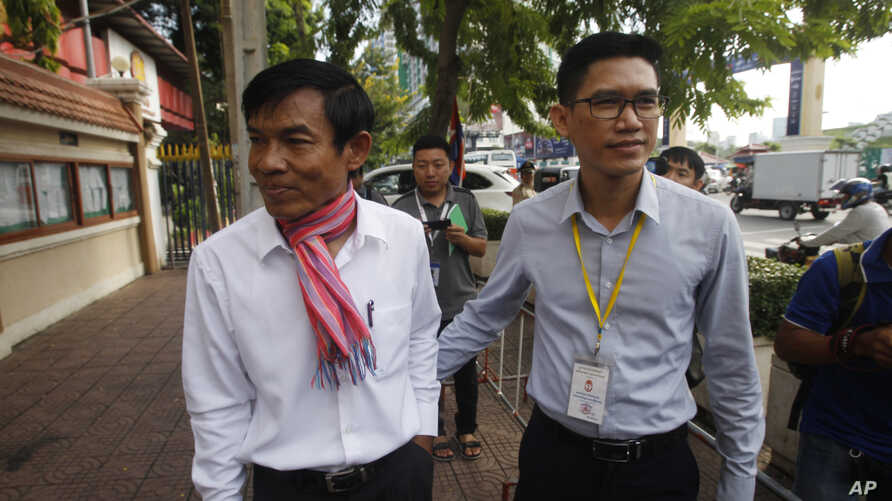 Journalists Uon Chhin, left, and Yeang Sothearin, right, arrive at the municipal court, in Phnom Penh, Cambodia, Thursday, Oct…