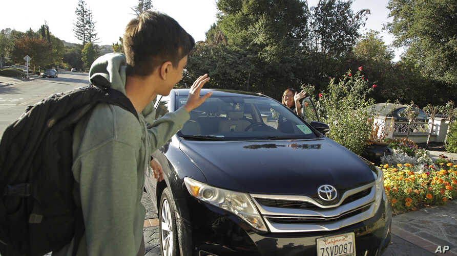 Zum driver Stacey Patrick, right, waves goodbye to student Saahas Kohli, left, as he returns home from school in Saratoga, California, Oct. 29, 2019.