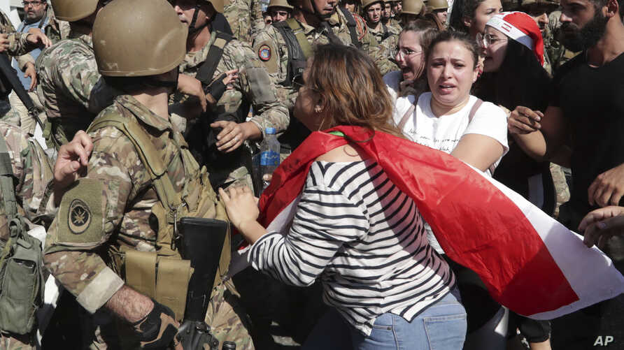 Anti-government protesters scuffle with Lebanese army soldiers in the town of Zouk Mosbeh, north of Beirut, Lebanon, Nov. 5, 2019.