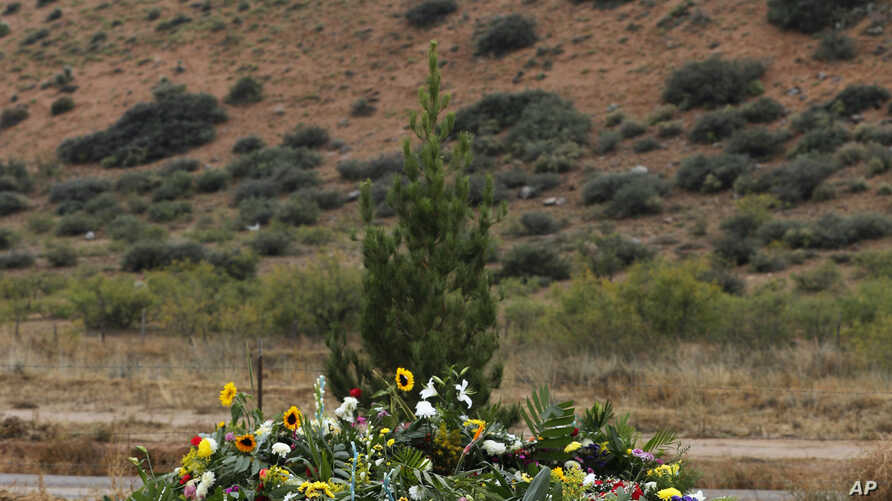 Freshly dug graves that contain the remains of Rhonita Miller and four of her young children are overspread with flowers a day…