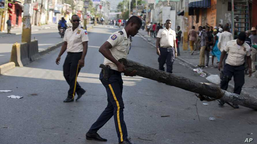 A national police officer removes a barricade in the street during a protest to demand the resignation of President Moise
