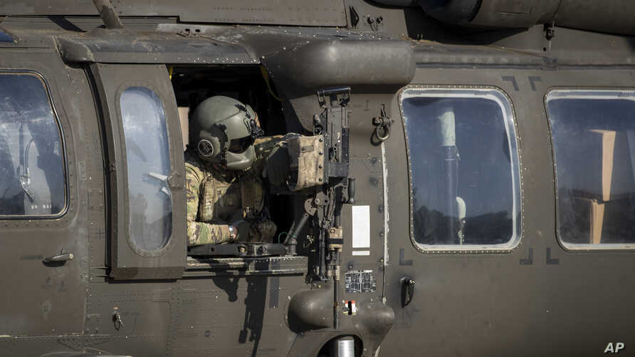 A helicopter gunner waits for takeoff at a US military base at an undisclosed location in Eastern Syria, Monday, Nov. 11, 2019…