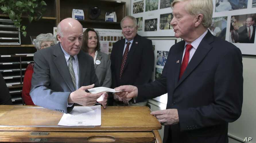 Republican presidential candidate former Massachusetts Gov. William Weld, right, hands paperwork to Secretary of State Bill Gardner as he files to have his name listed on the New Hampshire primary ballot, Nov. 13, 2019, in Concord, N.H.