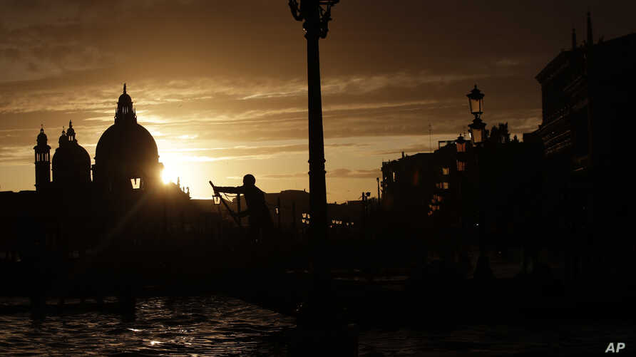 In this photo taken on Sunday, Nov. 17, 2019, a gondolier is silhouetted in a golden sunset in Venice, Italy. Venetians are fed…