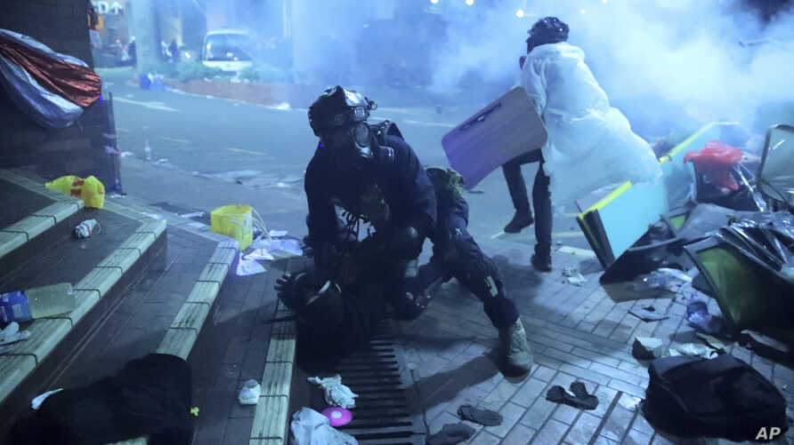 A policeman in riot gear detains a protester outside of Hong Kong Polytechnic University as police storm the campus in Hong Kong, early Monday, Nov. 18, 2019.