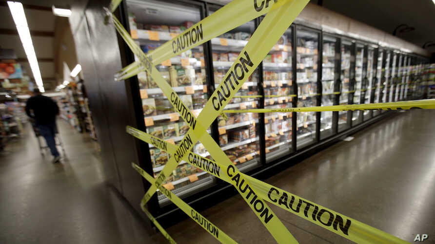 FILE - In this Oct. 31, 2019, file photo, a customer walks past the off-limits frozen foods section of Big John's Market in…