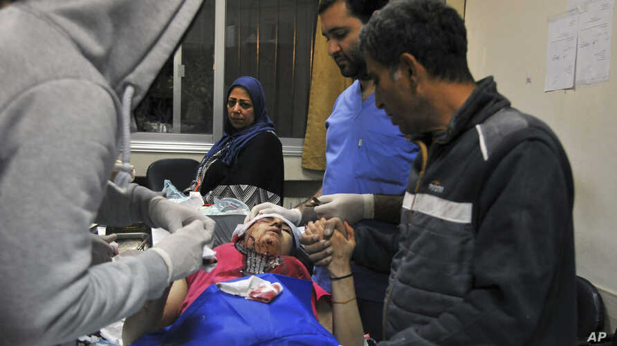 In this photo released by the Syrian official news agency SANA, a paramedic treats an injured woman wounded by Israeli missile strikes at a hospital in Damascus, Syria, Nov. 20, 2019.