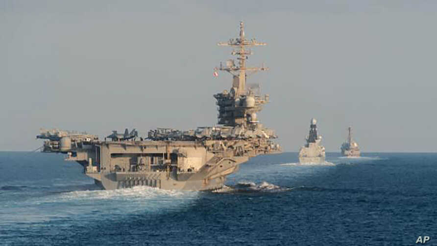 In this Tuesday, Nov. 19, 2019, photo made available by U.S. Navy, the aircraft carrier USS Abraham Lincoln, left, the air…