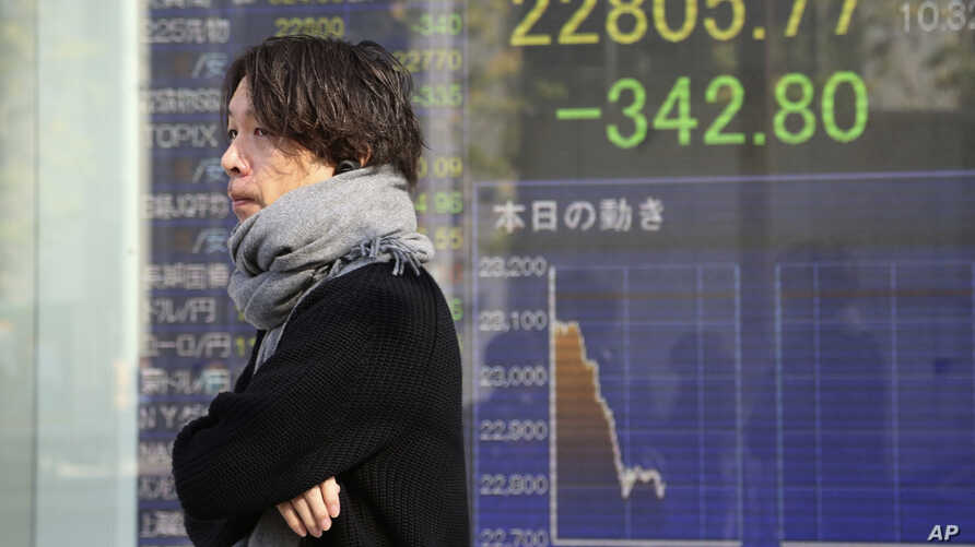 A man walks by an electronic stock board of a securities firm in Tokyo, Nov. 21, 2019.