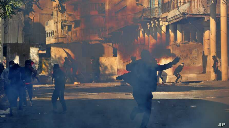 Riot police fire tear gas while blocking Rasheed Street during clashes with anti-government demonstrators in Baghdad, Iraq, Nov. 22, 2019.