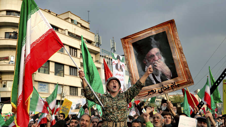 A demonstrator chants slogans while holding up an Iranian national flag during a pro-government rally denouncing last week's violent protests over a fuel price hike in Tehran, Iran,  Nov. 25, 2019.