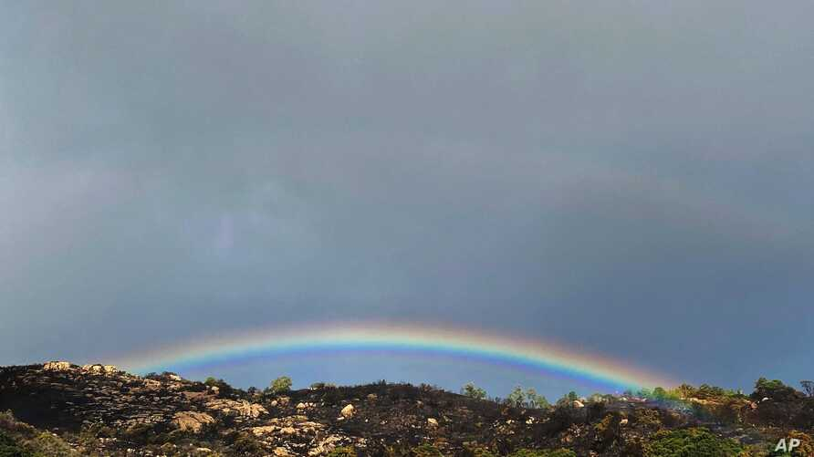 This photo tweeted by the Santa Barbara County Fire Department shows small smoke still smoldering below with a rainbow appearing above the burn scar area near Painted Cave Road in Santa Barbara, California.