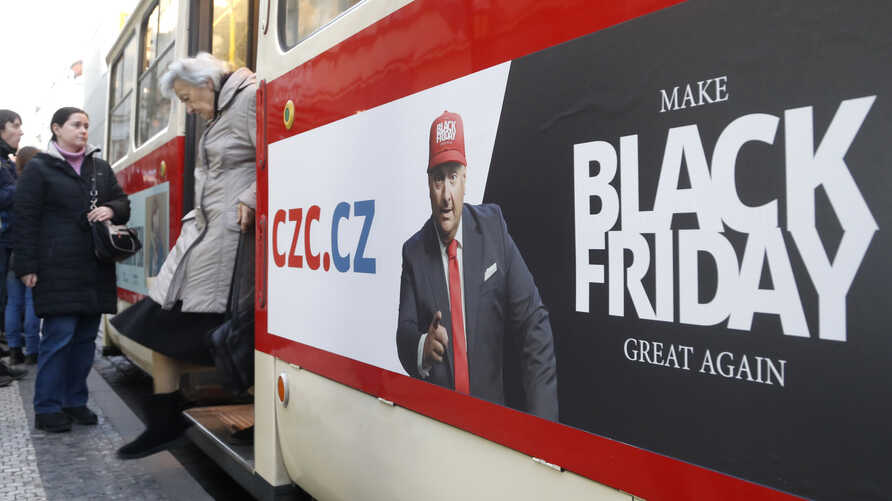 A woman gets off a tram advertising the Black Friday in Prague, Czech Republic, Nov. 28, 2019.