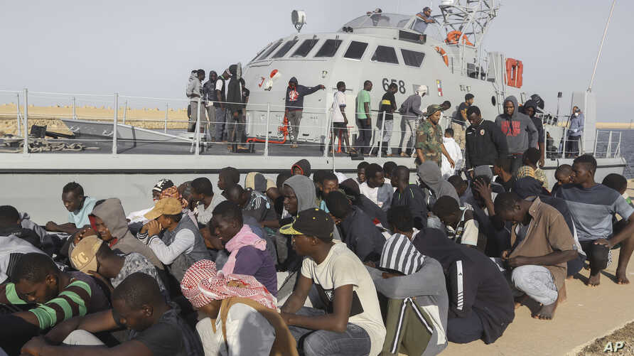 FILE - Rescued migrants are seated next to a coast guard boat in the city of Khoms, around 120 kilometers (75 miles) east of Tripoli, Libya, Oct. 1, 2019.