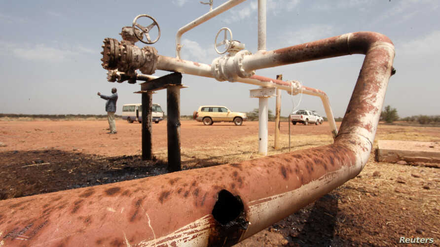 Oil spills onto the ground from an oil well head strafed by shrapnel from a bomb dropped by fighter jets at the El Nar oil…
