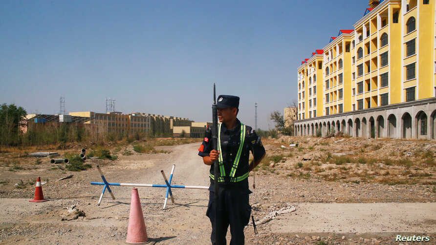 A Chinese police officer takes his position by the road near what is officially called a vocational education centre in Yining…