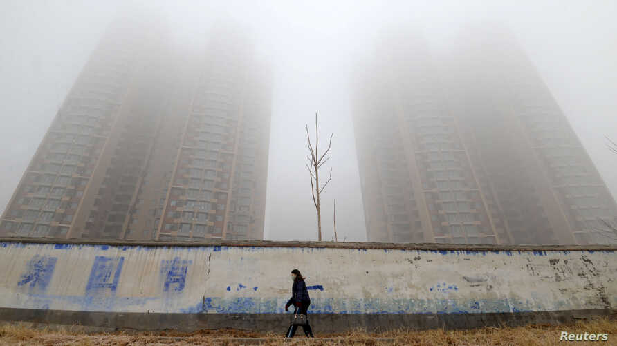 A woman wearing a mask walks past buildings on a polluted day in Handan, Hebei province, China January 12, 2019. REUTERS…
