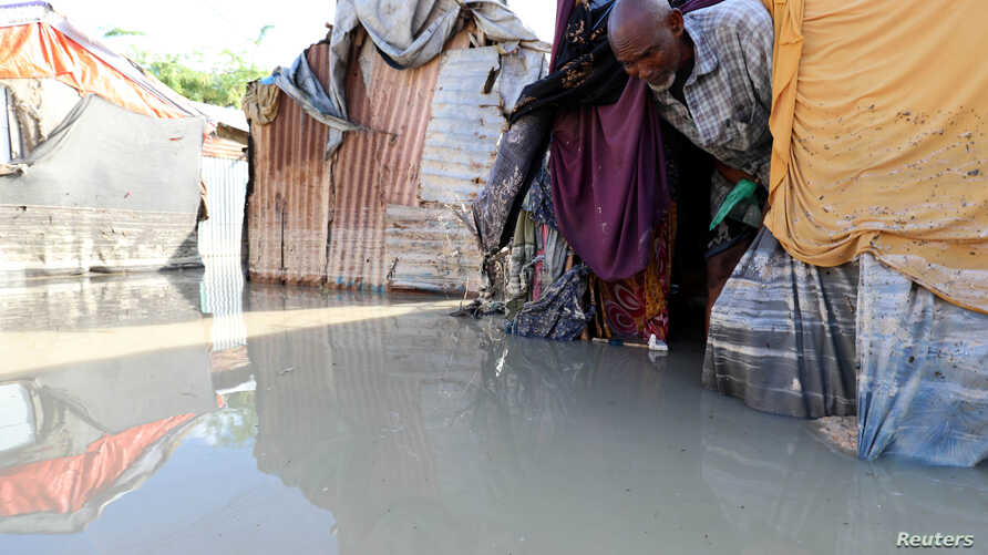 A Somali man walks out of his flooded makeshift shelter after heavy rain in Mogadishu, Somalia October 21, 2019.