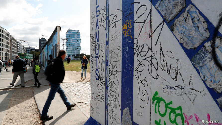 A pedestrian walks past segments of the East Side Gallery, the largest remaining part of the former Berlin Wall, in Berlin,…