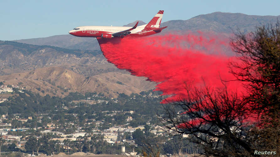 A plane drops fire retardant on the Maria Fire in the early morning in Santa Paula, California, U.S. November 1, 2019.   …