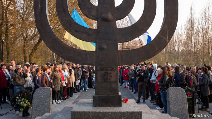 People hold a march against anti-semitism and nazism near a monument commemorating the victims of Babyn Yar (Babiy Yar), one of…