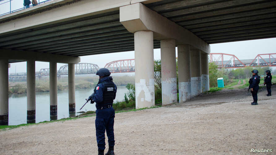 Mexican federal police officers stand on the bank of the Rio Bravo near a bridge connecting Eagle Pass, Texas, with Piedras…