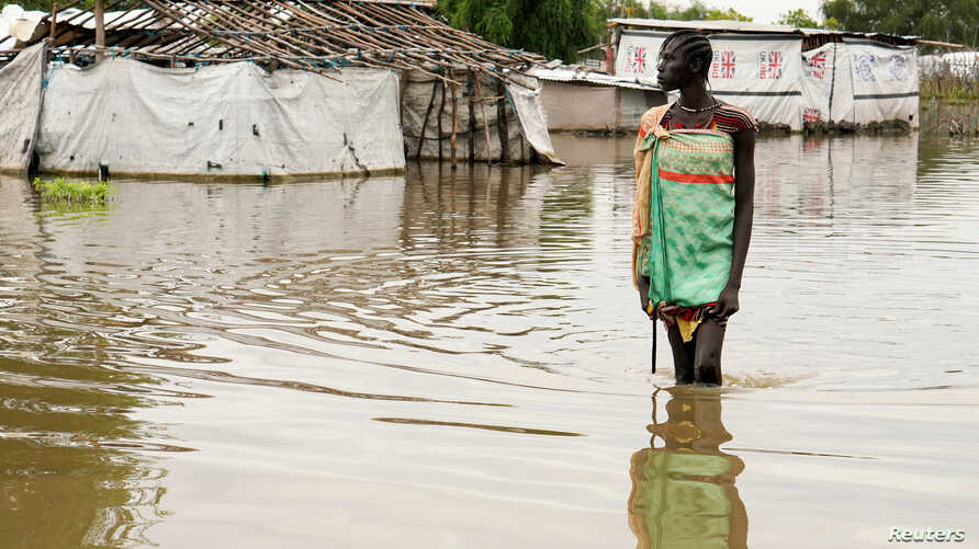 A girl walks in water after heavy rains and floods forced hundreds of thousands of people to leave their homes, in the town of Pibor, Boma state, South Sudan, Nov. 6, 2019.