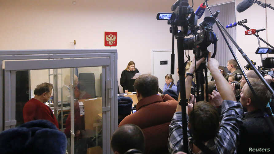 Russian historian and professor Oleg Sokolov, who is accused of murdering his girl friend and former student, stands inside a defendants' cage during a court hearing in Saint Petersburg, Russia, Nov. 11, 2019.