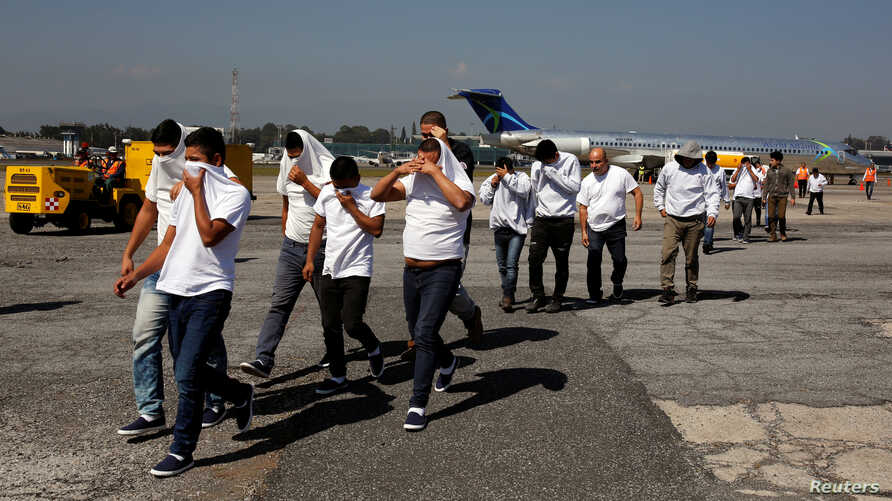 Guatemalan migrants walk on the tarmac after being deported from U.S., at La Aurora International airport in Guatemala City,…