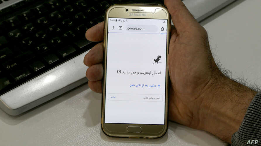 FILE - A man holds a smartphone connected to a Wifi network without internet access, at an office in the Iranian capital Tehran, Nov. 17, 2019.