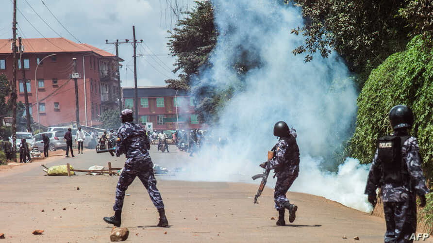 Uganda police officers conftont students of Makerere university during their protest against the 15 percent tuition increment in Kampala, Oct. 30, 2019.