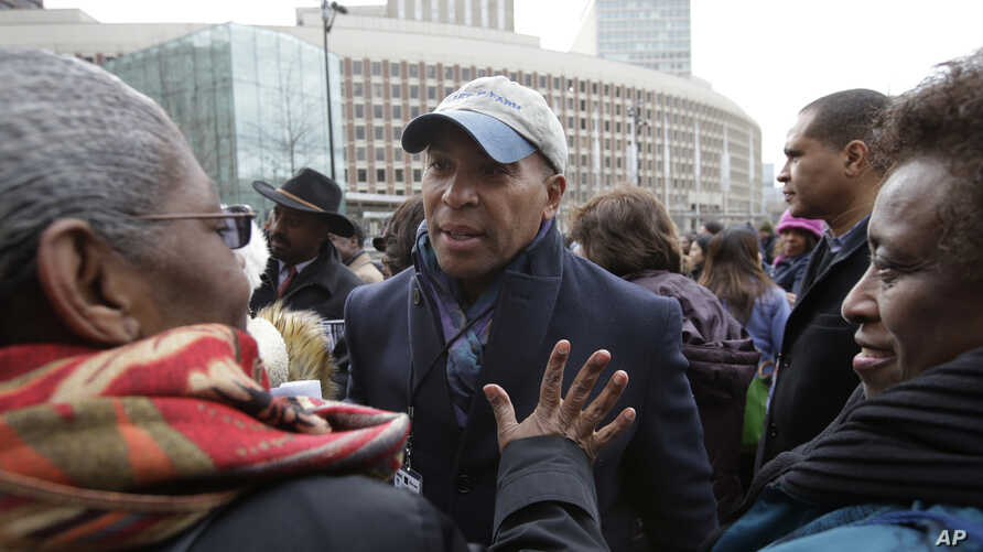 Former Mass. Gov. Deval Patrick, center, greets people in a crowd, April 2, 2018, before a remembrance on City Hall Plaza, in Boston.