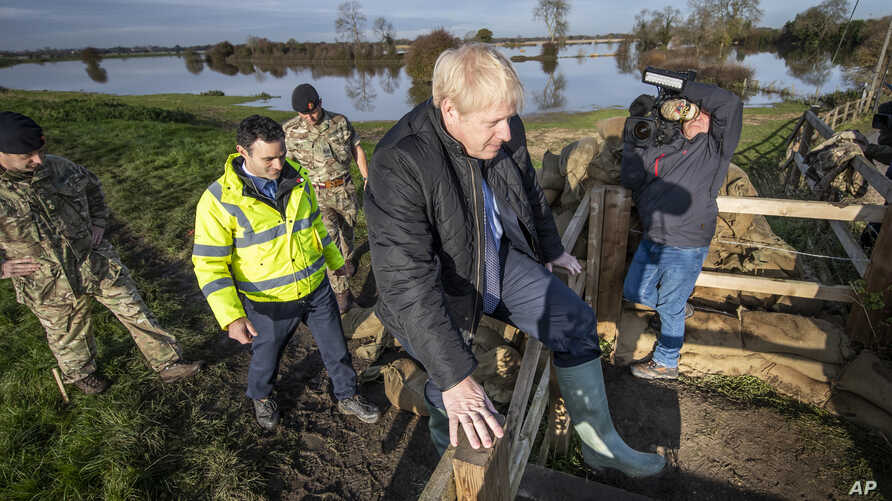 Britain's Prime Minister Boris Johnson climbs over a fence during a visit to see the effects of recent flooding, in Stainforth, England, Nov. 13, 2019.