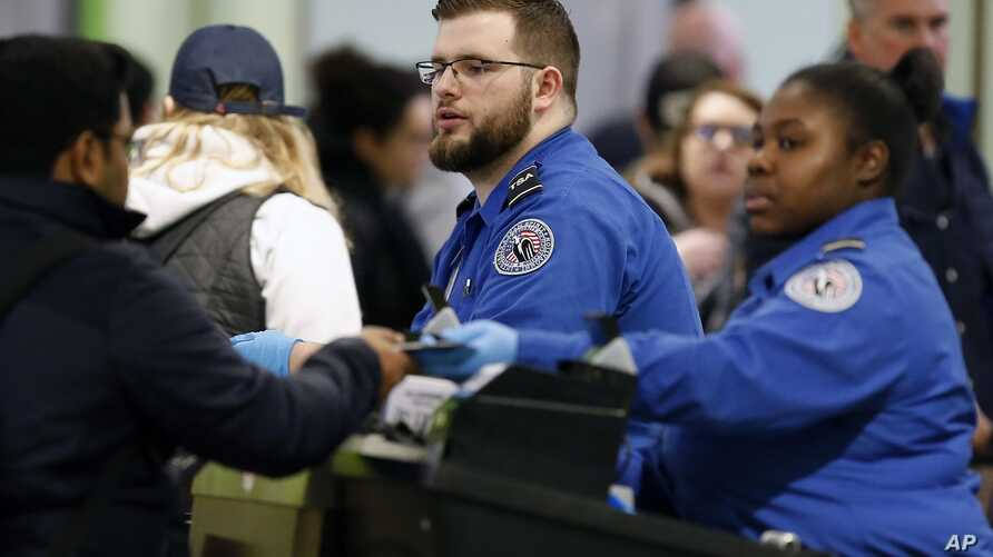 FILE - Transportation Security Administration officers work at a checkpoint at Logan International Airport in Boston, Massachusetts, Jan. 5, 2019.