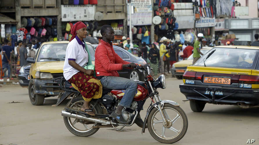A motorbike taxi rides past Mokolo Market in Yaounde, Cameroon, Oct. 11, 2018.