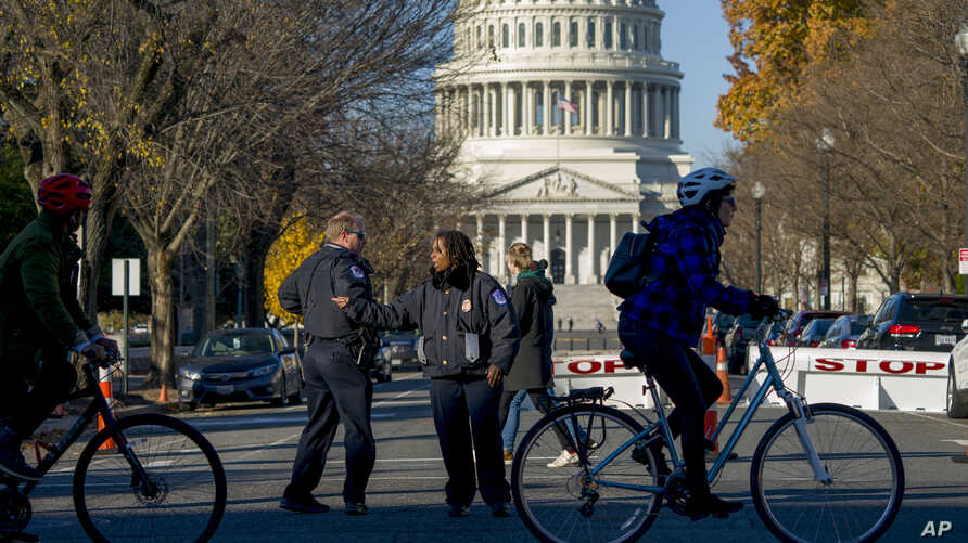 People are kept at a safe distance as the U.S. Capitol and its office buildings were briefly evacuated amid concerns over a small aircraft in the area, in Washington, Nov. 26, 2019.