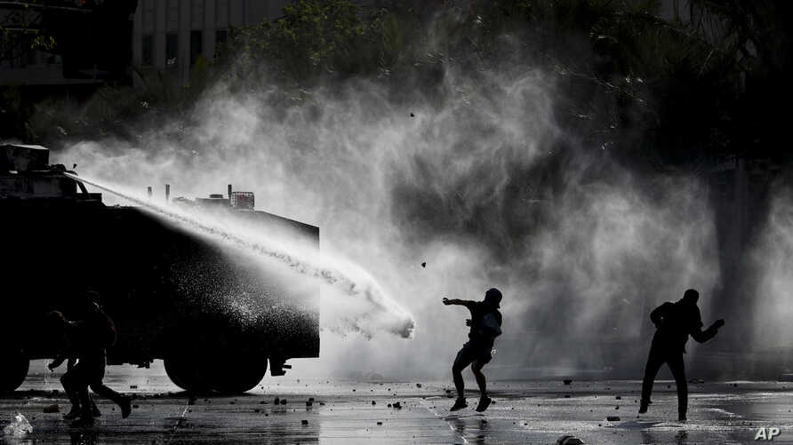 Police spray demonstrators with a water cannon during an anti-government protest in Santiago, Chile, Nov. 5, 2019.