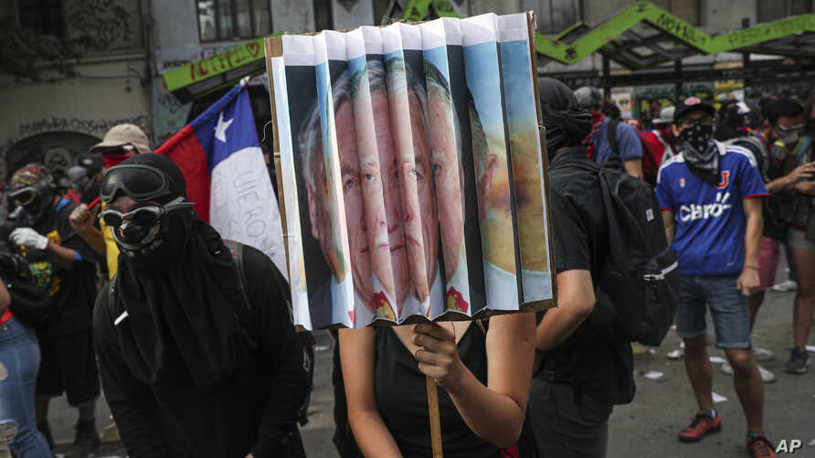 Anti-government protester hold a sign with the portraits of the Chile's President Sebastian Pinera and late military dictator Gen. Augusto Pinochet, during a protest in Santiago, Chile, Nov. 18, 2019.