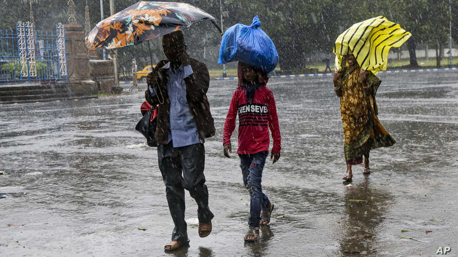 Indians walk in the rain in Kolkata, India, Nov. 9, 2019. Authorities in nearby Bangladesh put more than 50,000 volunteers on standby and readied about 5,000 shelters as Cyclone BulBul is expected to hit the low-lying nation's southern coast late Saturday