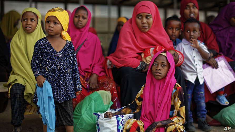 FILE - Somali refugee families wait to be flown to Kismayo in Somalia under a voluntary repatriation program, at the airstrip of Dadaab refugee camp, in northern Kenya, Dec. 19, 2017.