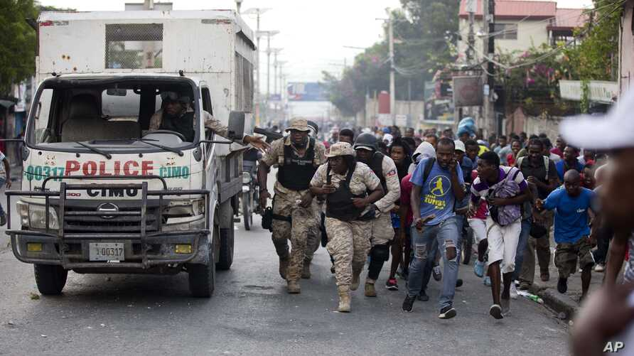Police officers and protesters take cover behind a police truck as shots ring out during a protest to demand the resignation of Haiti's president Jovenel Moise on the 216th anniversary of the Battle of Vertieres in Port-au-Prince, Haiti, Nov. 18, 2019.