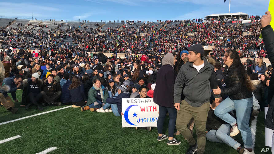 Demonstrators stage a protest on the field at the Yale Bowl disrupting the start of the second half of an NCAA college football game between Harvard and Yale, in New Haven, Connecticut, Nov. 23, 2019.