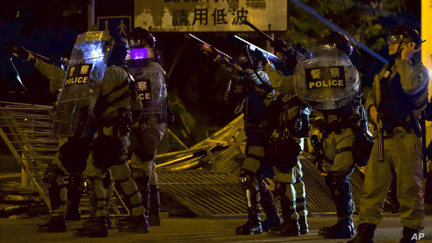 Police in riot gear react to protesters near the University of Hong Kong, in Hong Kong, Nov. 16, 2019.