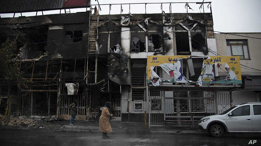 In a photo taken Nov. 18, 2019, and released by the Iranian Students' News Agency, ISNA, people walk past buildings which burned during protests that followed the authorities' decision to raise gasoline prices, in the city of Karaj, west of Tehran.