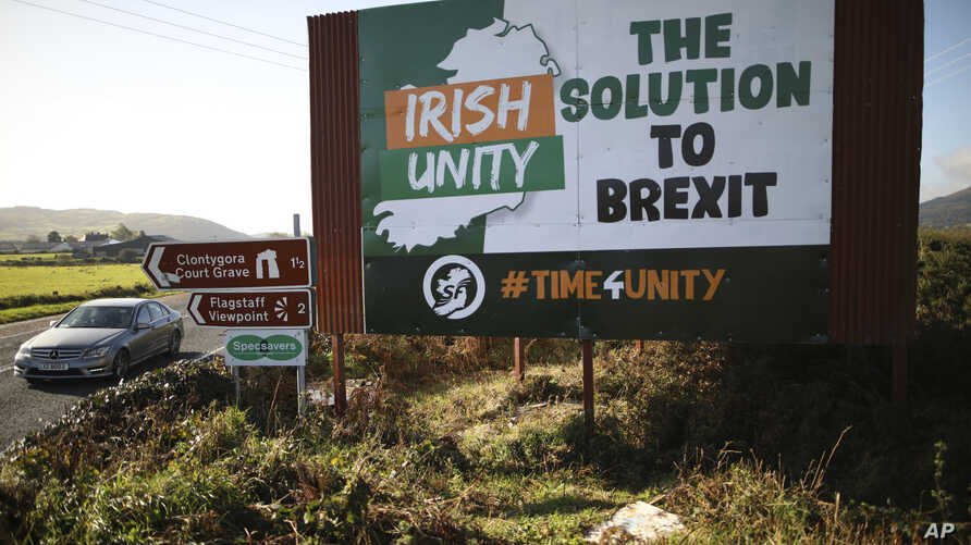 FILE - A car passes a Brexit sign on the old Belfast to Dublin road, close to the Irish border in Newry, Northern Ireland, Oct. 16, 2019.
