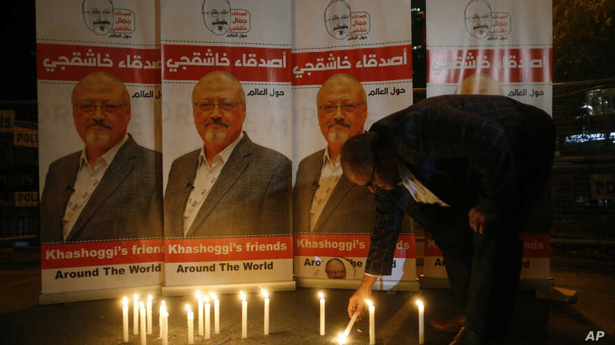 FILE - An man lights a candle during a candlelight vigil for Saudi journalist Jamal Khashoggi outside Saudi Arabia's consulate in Istanbul, Turkey, Oct. 25, 2018.