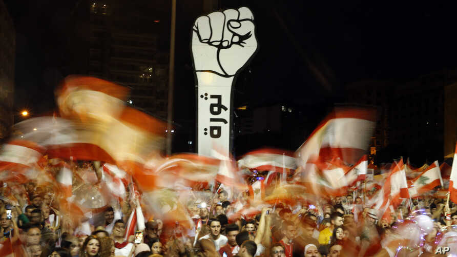"""FILE - Protesters wave Lebanese flags during an anti-government protest in Beirut, Lebanon, Nov. 10, 2019. The Arabic writing beneath the fist reads """"Revolution."""""""