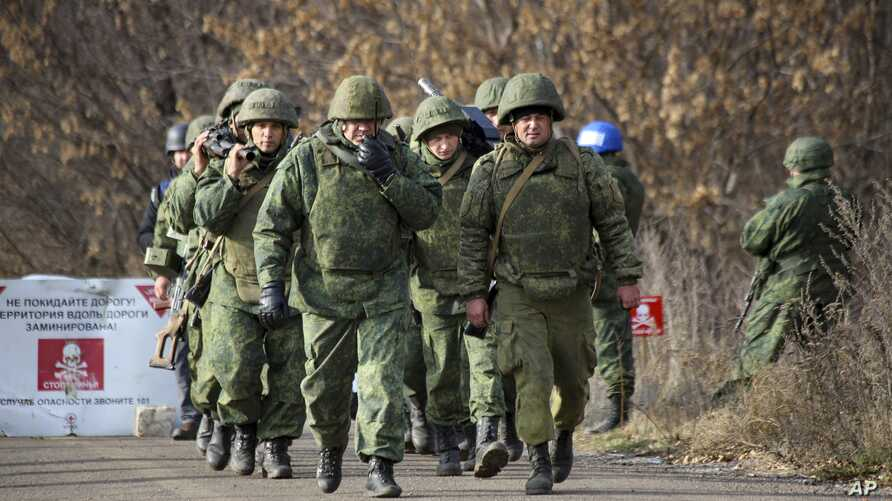 Russia-backed separatist rebels' unit walk to take their position at the new line of contact outside Petrivske, Ukraine, Nov. 9, 2019.