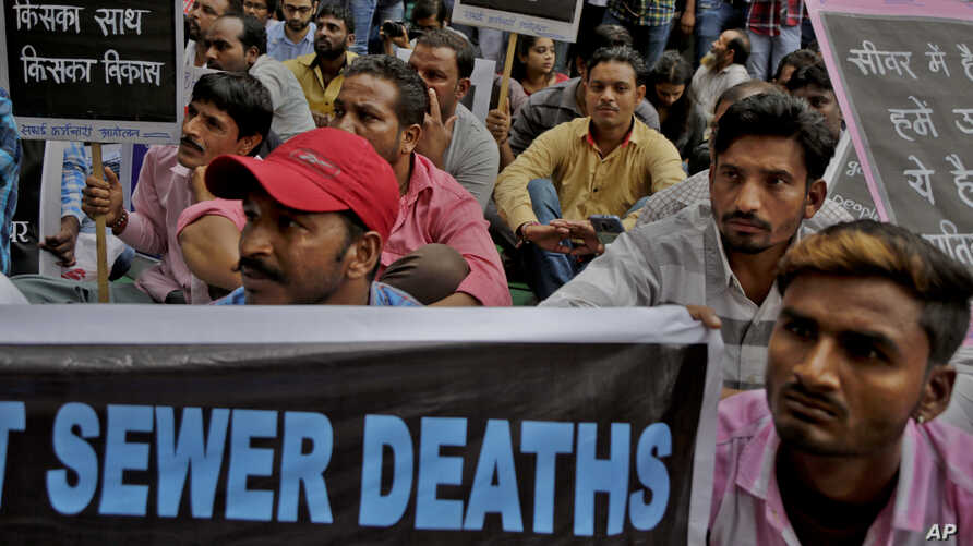 FILE - Sewer cleaning workers and others sit during a protest near the Indian parliament calling for safer working conditions following the deaths of several sanitation employees, in New Delhi, India, Sept.25, 2018.